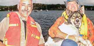 Skipper, the Fishin' Technician's sidekick for the past 15 years, accepts a cuddle from the late Jack Layton, leader of the federal New Democratic Party, during a day's fishing with former Western Arctic MP Dennis Bevington in 2006. Skipper died Sunday after a lifetime of fishin' with all kinds of Technician guests, famous or otherwise. NNSL file photo