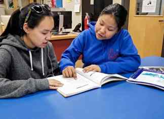 Grade 11 student Lydia Kaviok, right, discusses some of the things she learned at the Youth Parliament in Iqaluit with her friend, Edith Issakiark, at John Arnalukjuak High School in Arviat on Dec. 7, 2018. Photo courtesy Gord Billard
