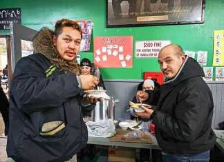 Silu Autut, left, and Troy Aksalnik are half grinny and half yummy as they load-up on some delicious chile at the Rankin Inlet arena on Feb. 10, 2019. Photo courtesy Noel Kaludjak