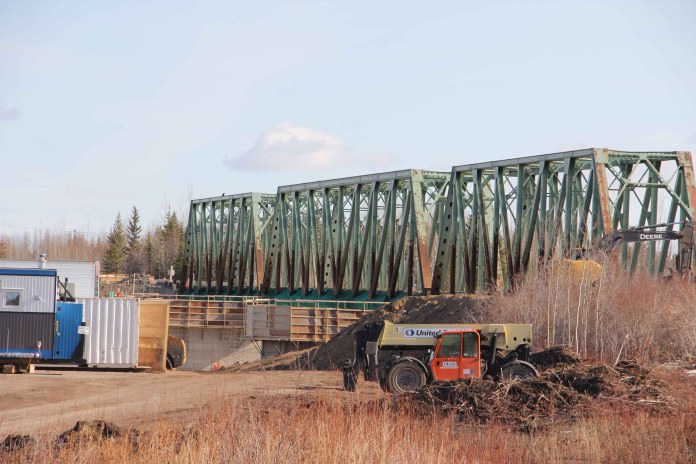 The superstructure of the Pine Point Bridge has been removed in the reconstruction of the span across the Hay River. Traffic is crossing the river on an old railway bridge. Paul Bickford/NNSL photo