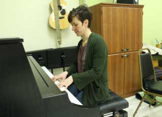 Mary Kelly plays a new piano she able to buy to help outfit her new business. It is one of several instruments she has available at Music Space. Brett McGarry/NNSL Photo