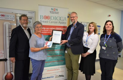 Director of the NNUH Breast Imaging Unit Dr Arne Juette, accompanied by members of his team, presents a Certificate of Appreciation to Judith Marney, and husband John.