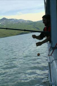 Chief Scientist, Patrick Ressler, attaches calibration spheres to the line that will be lowered beneath the ship.