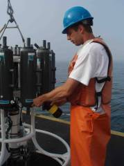 "Justin Czarka collects water samples to use in nutrient and chlorophyll research.  While on the deck during ""ops"" (operation) all personnel must wear a life jacket and hardhat."