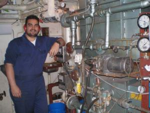 Jake DeMello stands by the desalination machine in the Miller Freeman's engine room.