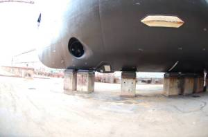 Underside of ship on the blocks; the black hole is on for anchor storage