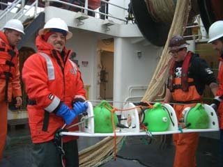 "Roy works with the deck crew to remove the ""pea pod"" from the trawl net."