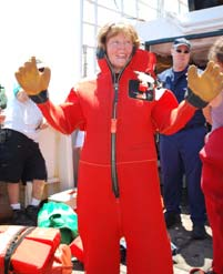 Laurie dons a survival suit during a ship safety briefing.