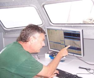 Chuck studying some of the side-scan sonar (SSS) data as it is relayed from the SSS 'towfish' to the launch's computer.