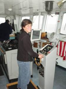 NOAA Teacher at Sea, Terry Welch, at the helm of the RAINIER