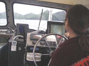 Leslie Abramson, Able Seaman and coxswain, steers the survey boat