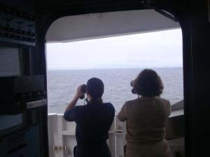 ENS Meghan McGovern on left, and ENS Olivia Hauser on right, RAINIER Junior Officers, looking at unmarked buoy sighted by officers on bridge of the RAINIER