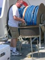 Patrick Downey, FREEDOM STAR cook, is preparing lunch on the barbeque.  The barbeque was designed and built by the crew and is securely bolted to the deck.