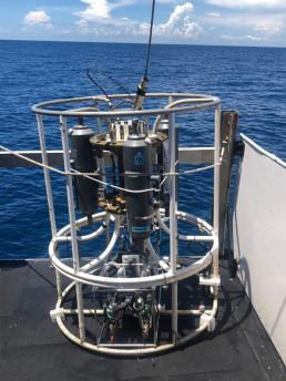 A CTD on deck with water in the background