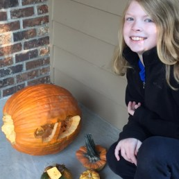 A student with a pumpkin carved to look like a fish.