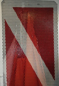 A red and white 'diver down' scuba flag painted on a metal storage locker door.