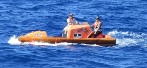 A smaller rigid rescue boat floats nearby, prepared to assist divers if needed.