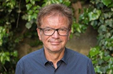 Rudolf Anschober lächelt vor grünem Hintergrund