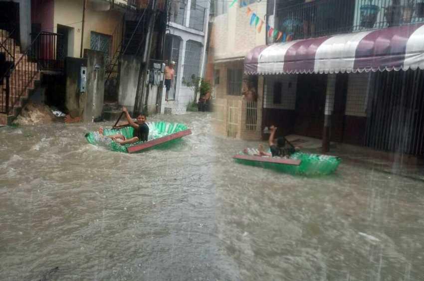 Jovens praticam esporte radical nas águas da chuva que caiu em Manaus