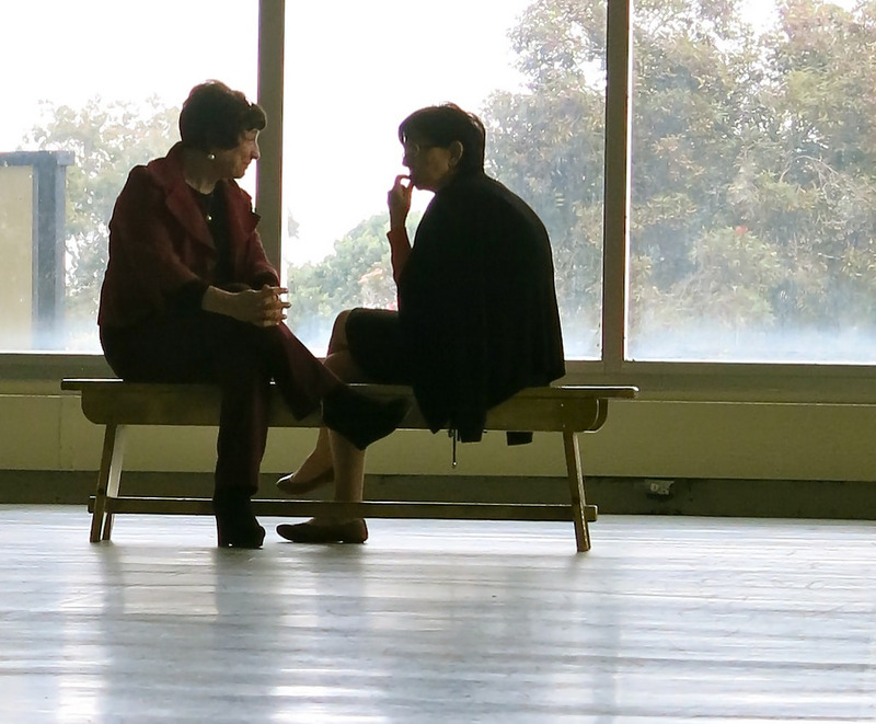 Two women sit having a quiet conversation in a public place.
