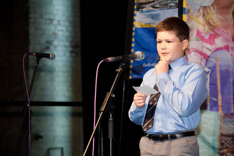 A boy holding a note card steps up to a microphone to give a public presentation.
