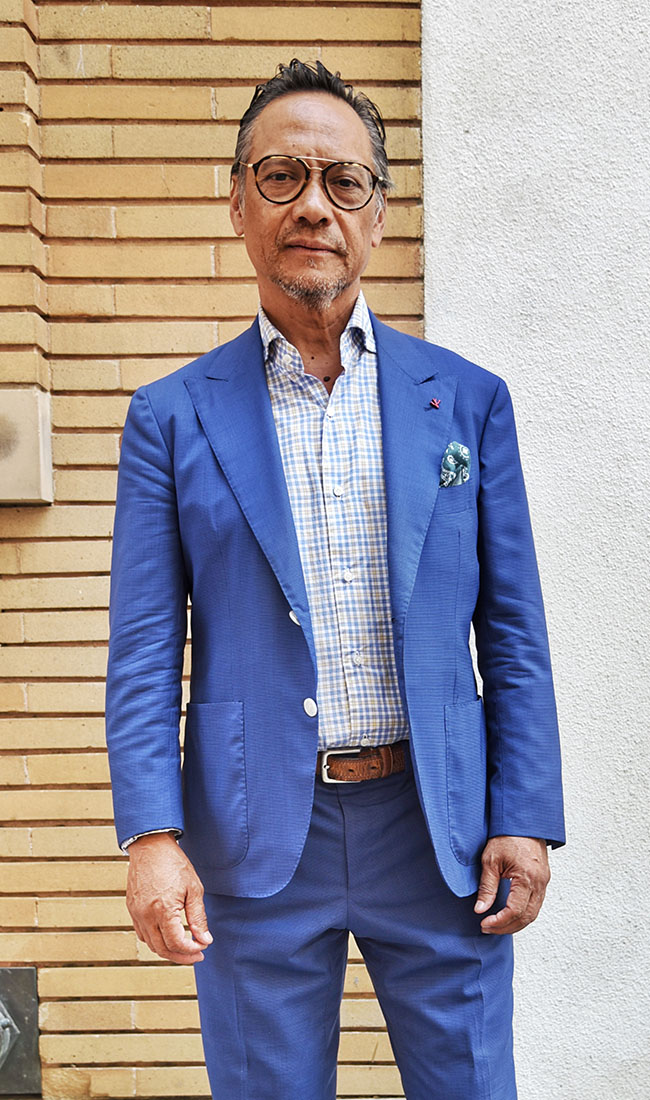 "Ric Baluyot from the East Bay was taking a break from his job as a sales assistant at Isaia. The weather directs his style choices for the day: ""Today the sky is blue, so I'm wearing a lighter fabric — I'm at ease.""  He's wearing Isaia — classic Neapolitan clothing from Italy. Suit and shirt: Isaia"