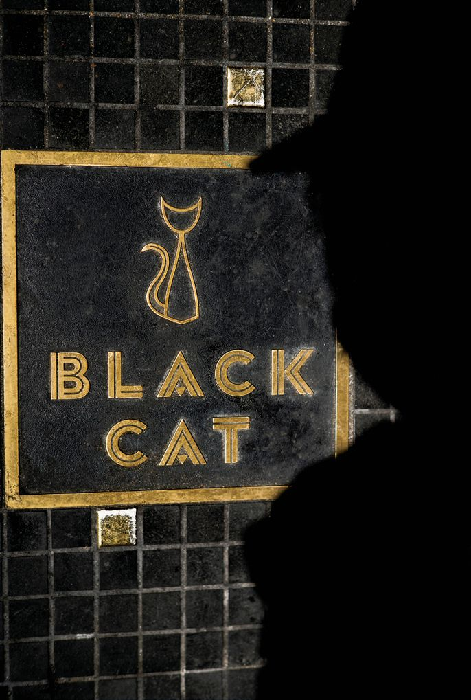 n arrangement of tiles and signage in front of the entrance to the Tenderloin's Black Cat, combined with the photographer's ambient shadow, add to the club's urban old-school noir vibe.