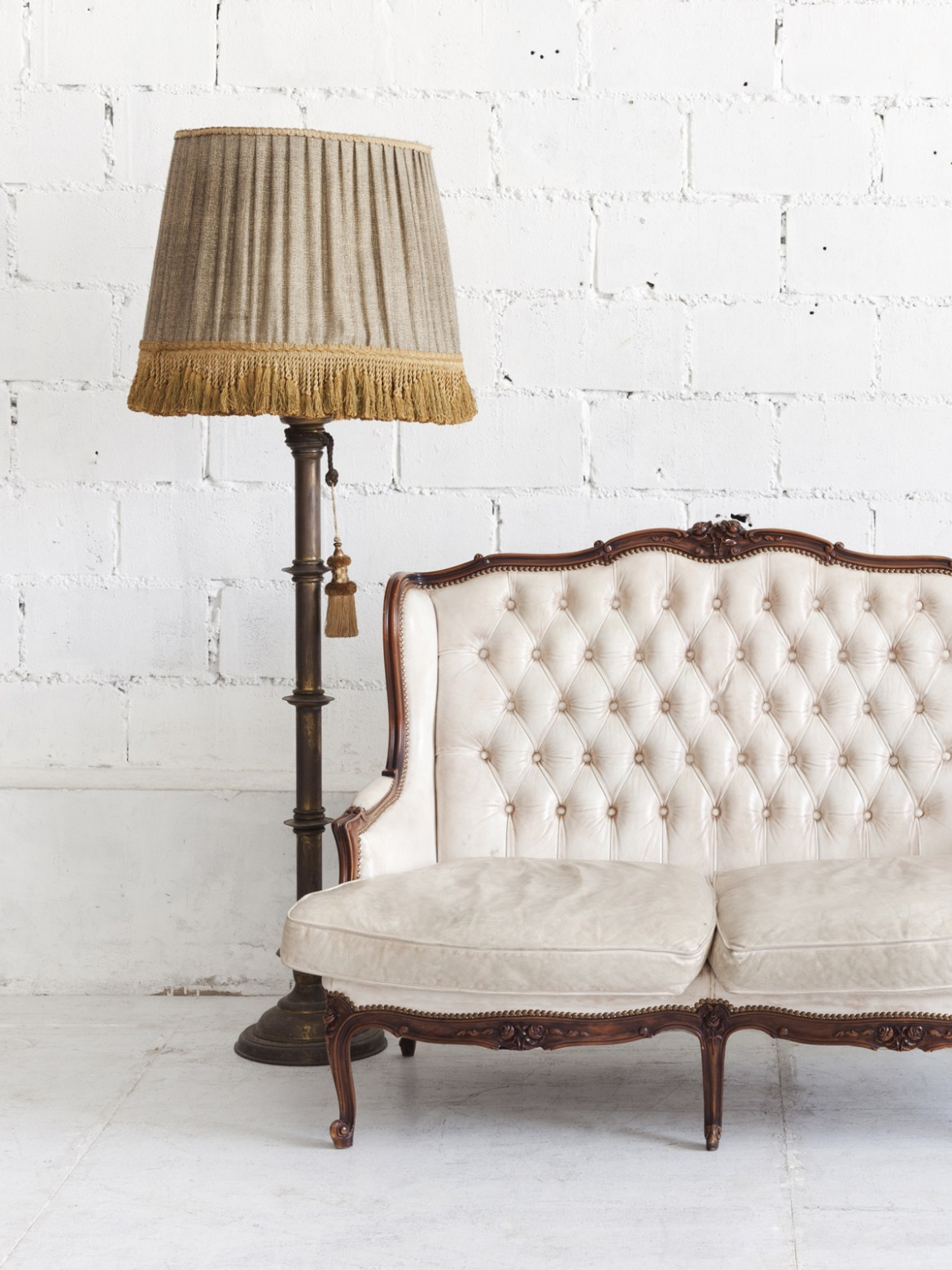 Antique white settee, lamp with fringed shade