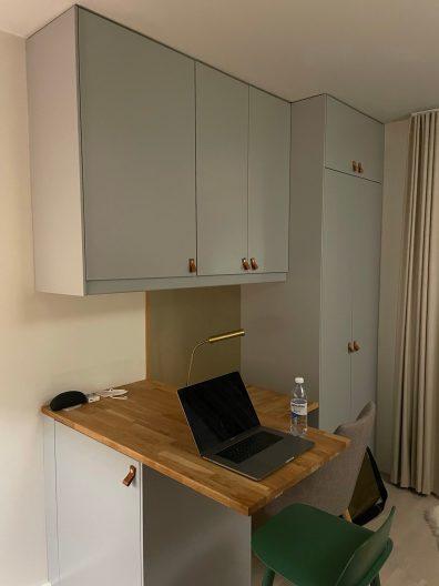 Esstisch mit Hocker, dahinter ein kleiner Schreibtisch mit Stuhl
