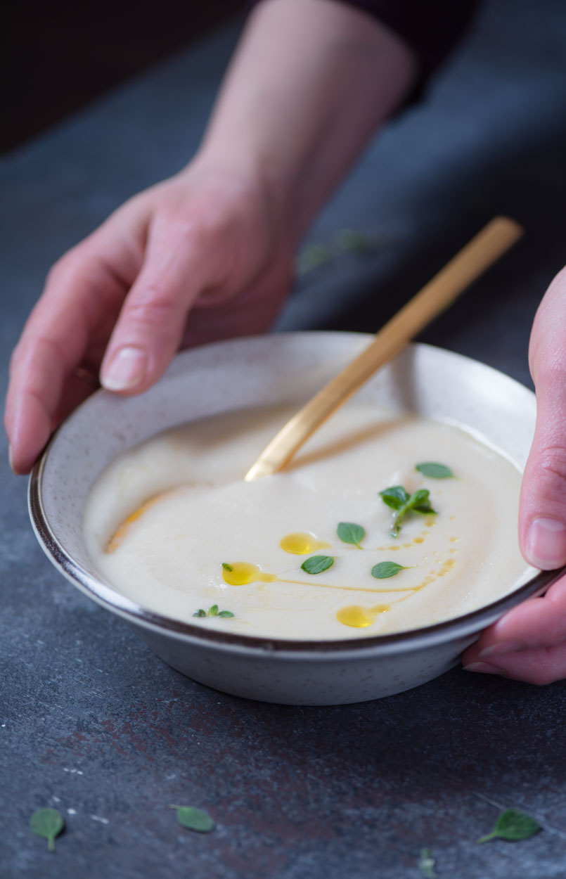 hands holding creamy cauliflower and parsnip soup garnished with fresh marjoram and olive oil drizzle
