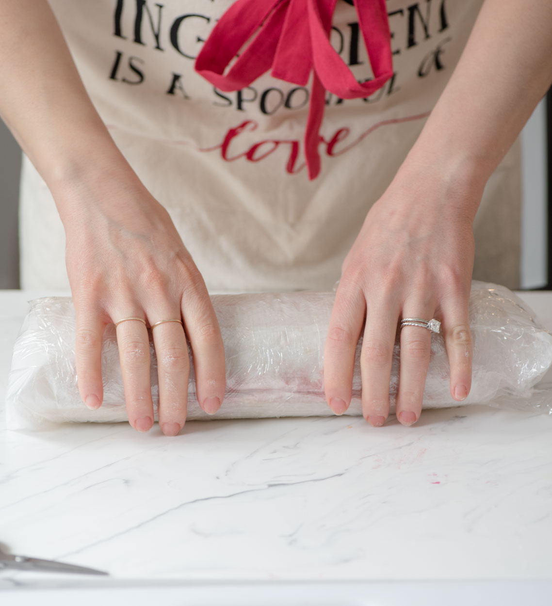 hands shown smoothing out and holding the cake roll covered in plastic wrap