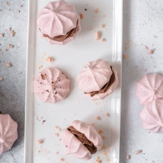 Pink pavlova cookie sandwiches filled with whipped fudge on a white plate