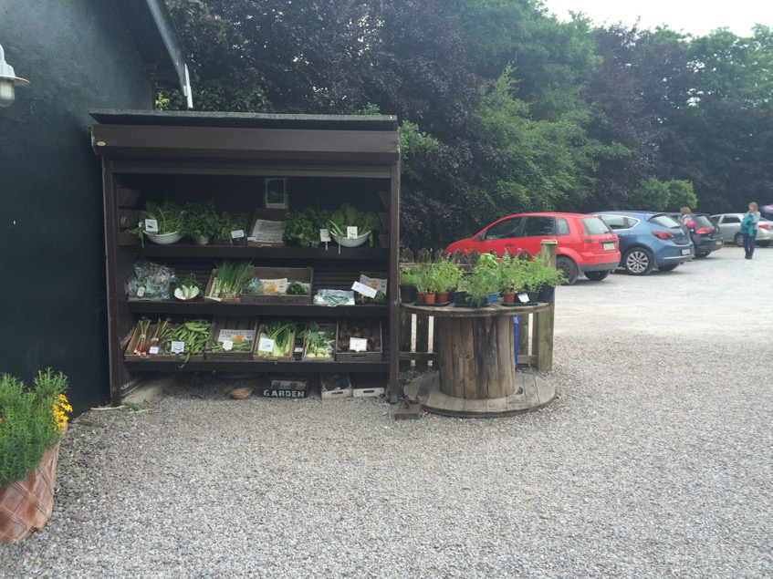Homegrown produce for sale outside the shop.