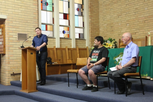Pascoe Vale candidates Forum: Liam Farrelly (Greens) sopeaking with Sean Brocklehurst (Socialist Alliance) and empty chair for the absent Labor and Liberal candidates. Forum organiser Robert Humphreys on right.