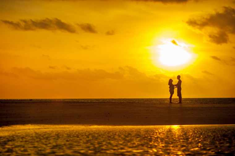 man and woman standing near seashore under sunset