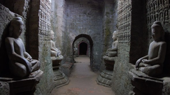 Budhas and carvings line the walls of a passageway