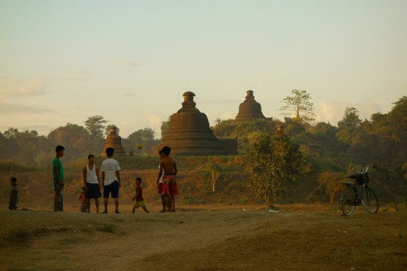 Kids playing football in front of temples