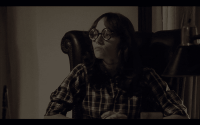 A girl with comical, round glasses sits in an office chair.