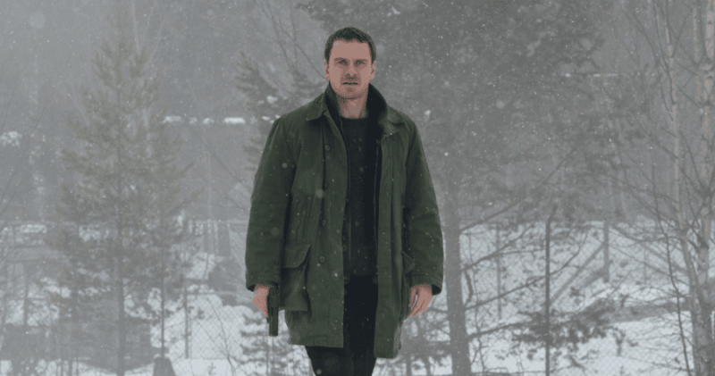 Michael Fassbender stands amid misty, gray woodland, a gun in hand.