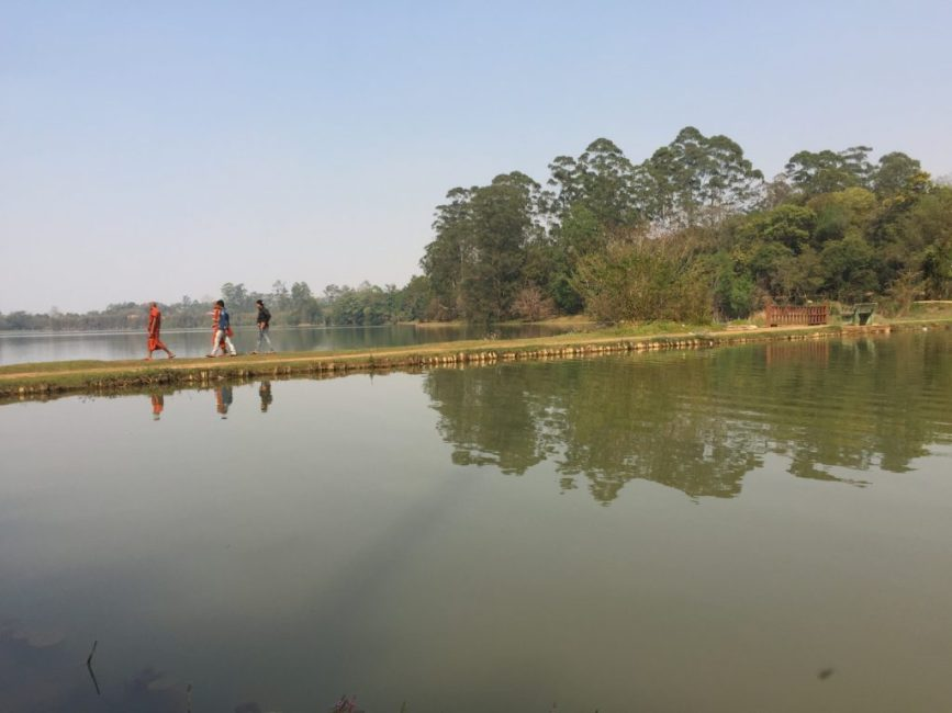 Three people crossing a lake while walking on a narrow strip of land