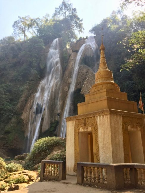 Small pagoda with waterfall flowing in the background