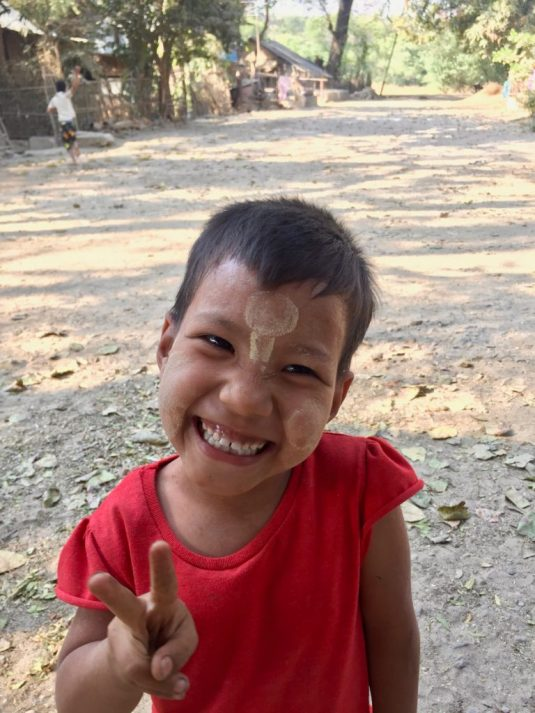 Burmese girl with red shirt smiling and flashing the peace sign