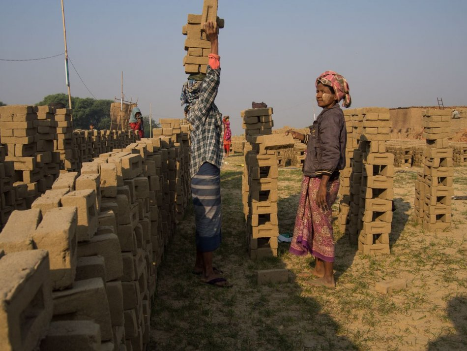Workers carrying and stacking bricks