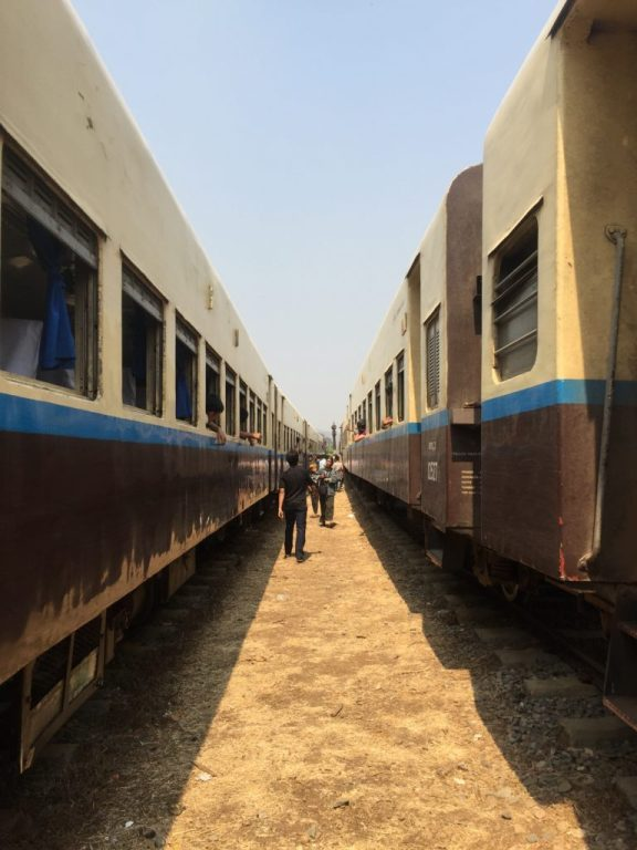 Two trains sit parallel to each other at a stop along the route between Hsipaw and Pyin Oo Lwin