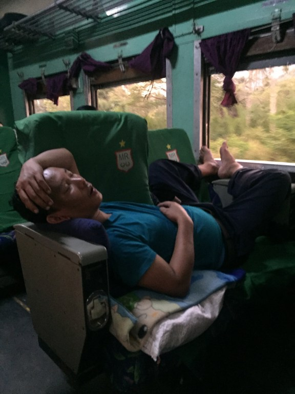 Sleeping man sprawled across two seats on the train to Mawlamyine