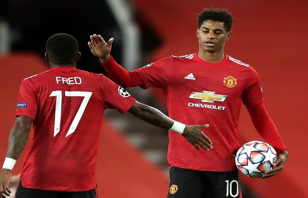 Marcus Rashford celebrates with Fred, clutching match ball after his first senior hattrick for Manchester United.