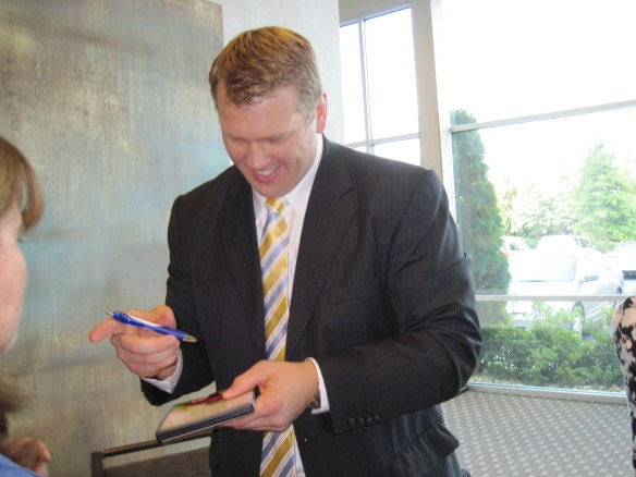"""Chris Nowinski, former WWE wrestler and co-founder and president of the Sports Legacy Institute, signing our copy of the """"Head Games"""" documentary."""