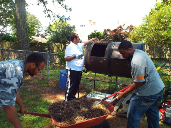 DJ, Zel, and Steve adding some old hay from our chicken coop into our compost tumbler!