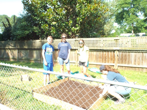 Youthworks kids building a raised strawberry bed for us.