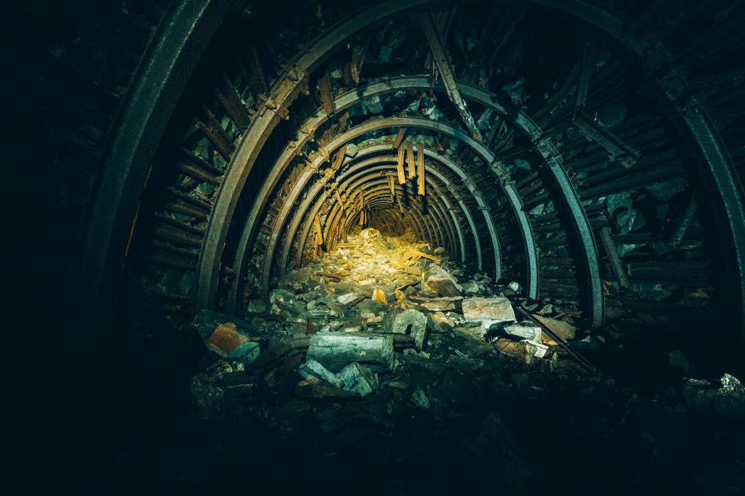 A mine shaft with a beam of light symbolizes the true treasure found in the analogy in Job 28.